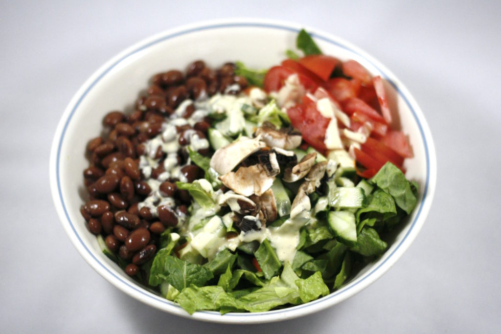 big buddha bowl with beans and ceasar dressing